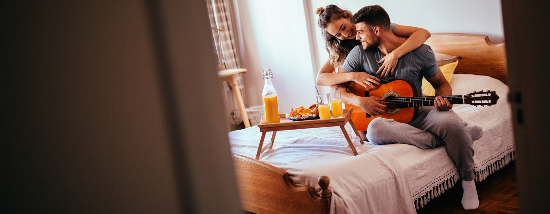 A couple is sitting on the bed playing an acoustic guitar.